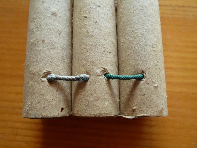 Propojení jednotlivých sopouchů zelenou zápalnou šňůrou. Délka této zápalné šňůry určuje dobu zpoždění mezi jednotlivými sopouchy.